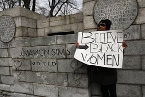 A woman stands beside the empty pedestal where a statue of J Marion Sims was taken down.