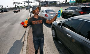 Man sells cold bottled drinks to motorist at a busy intersection on June 20, 2017 in Phoenix, Arizona.