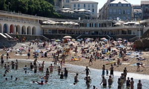 People sunbathe and swim at the at the Port-Vieux beach in Biarritz, southwestern France, on 30 July.