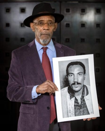 Linton Kwesi Johnson holds a portrait of Amanuel Asrat.