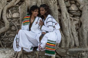 Two women pose by the trees in Gondar before the festival begins