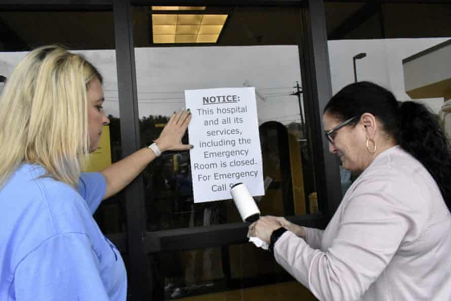 Medical workers tape a notice on the emergency room door of Fairmont Regional Medical Center in Fairmont, West Virginia, after the hospital closed.