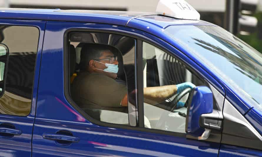 A taxi driver wearing a protective face mask driving in Bristol