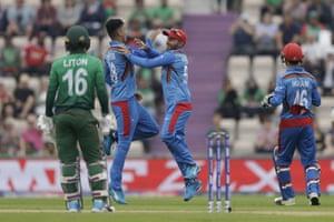 Afghanistan's Hashmatullah Shahidi celebrates with bowler Mujeeb Ur Rahman after catching out Bangladesh's Liton Das.