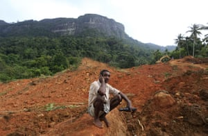 A Sri Lankan mudslide survivor sits watching military rescue work at the site of a mudslide in Kiribathgala village on 29 May 2017