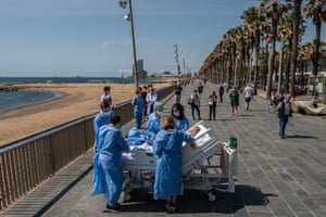 Hospital patient Isidre Correa is taken to the seaside by intensive heath care staff outside the Hospital del Mar in Barcelona.