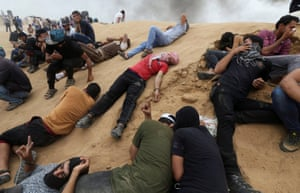 Palestinian demonstrators react to teargas fired by Israeli forces during a protest demanding the right to return to their homeland at the border between Israel and Gaza in the southern Gaza Strip.