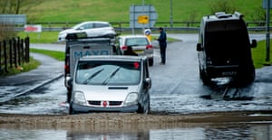 Cars make their way through floodwater in Accrington