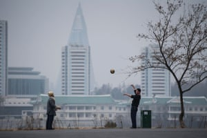 Men play with a ball in the park