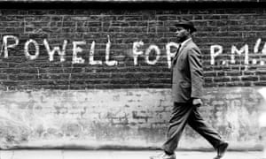 A black man walking past graffiti stating 'Powell For PM' in 1968.