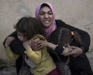 A woman holds her daughters as gunshots are heard in a neighbourhood recently liberated by Iraqi security forces in western Mosul, Iraq.