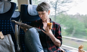 A woman on a train eating a snack