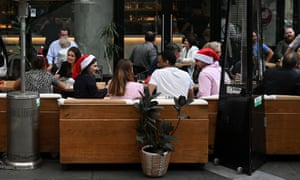 People wear Santa hats at a bar and eatery in the city centre following further easing of coronavirus restrictions in Sydney, Australia.