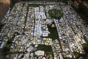 An Egyptian book restorer lays out burnt and damaged books to dry in the garden of the Institute of Egypt after the centre caught fire during deadly clashes between security forces and protesters.