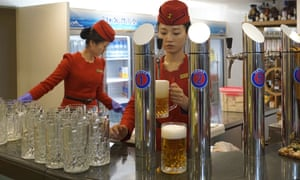 Waitresses on board a restaurant boat in Pyongyang pour beer for customers.