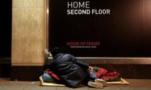 A homeless man sleeps on the street.