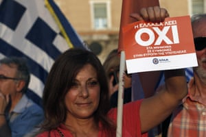 A supporter of NO vote in the upcoming referendum, holds a placard reads ''Greece says NO'' during a rally at Syntagma square in Athens on Monday, June 29, 2015. Anxious Greek pensioners swarmed closed bank branches and long lines snaked at ATMs as Greeks endured the first day of serious controls on their daily economic lives ahead of a July 5 referendum that could determine whether the country has to ditch the euro currency and return to the drachma. (AP Photo/Petros Karadjias)