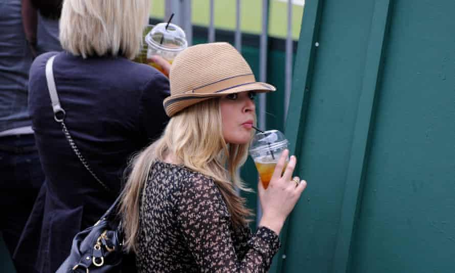 A woman drinks a Pimm's before watching a match at Wimbledon