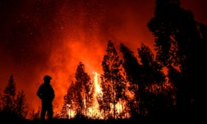 A firefighter watches the progression of a wildfire in Mação