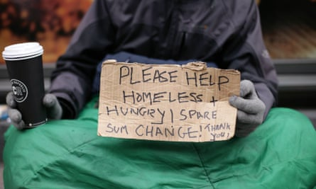 Homeless person holds out sign asking for money.