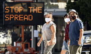 People wearing masks in front of a coronavirus sign are urging citizens to