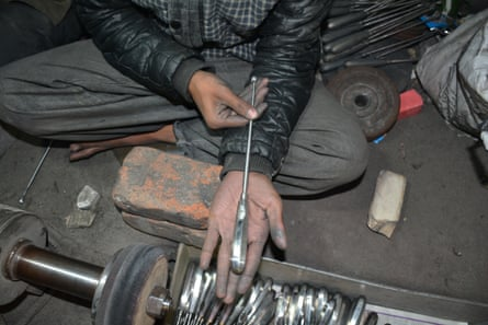 A child in a surgical instrument workshop in Sialkot, Pakistan, shows a spoon-shaped curette he has just finished polishing