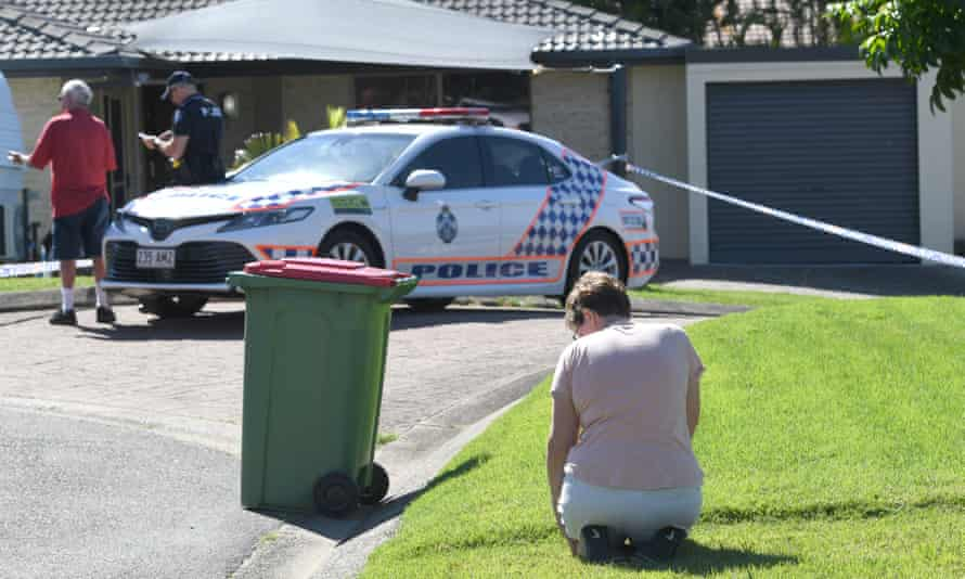 Arundel resident Louise Christy is seen kneeling in mourning outside the home of murder victim Kelly Wilkinson on the Gold Coast, Australia