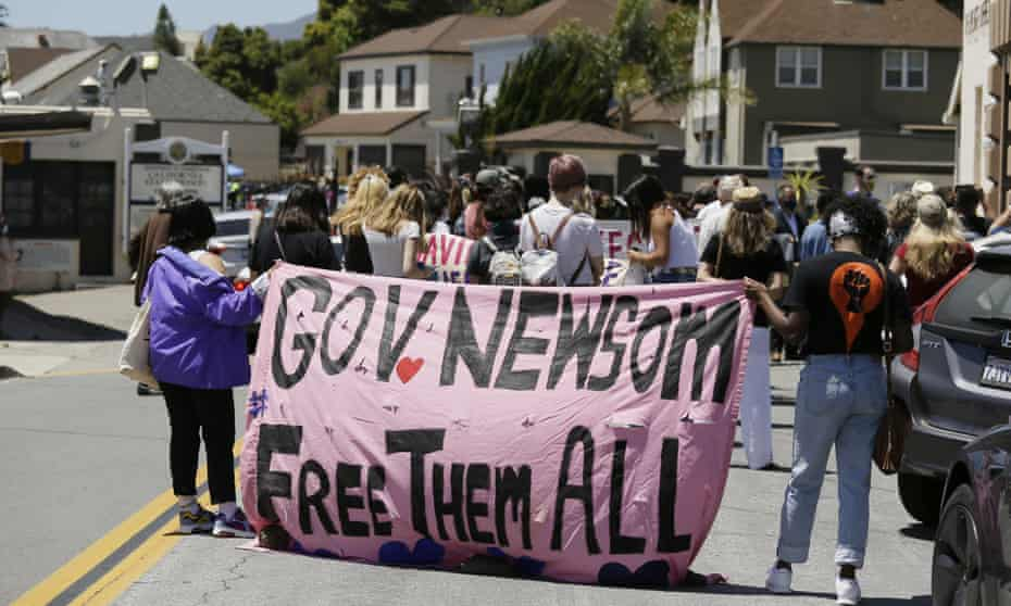 Two women hold up a banner urging California governor Gavin Newsom to free prisoners during a news conference outside San Quentin State Prison Thursday, July 9, 2020