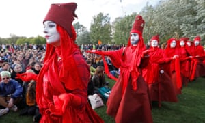 Extinction Rebellion activists dressed in red robes with white makeup