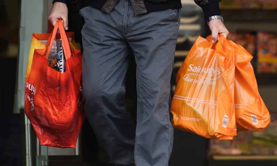 A shopper holding Sainsbury's bags