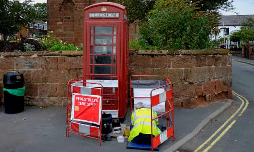 A BT telephone engineer carries out work outside a traditional British Telecom red telephone box