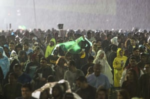 Spectators walk in the rain during the Vive Latino rock music festival in Mexico City on Sunday.