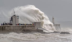 Crowds gather to watch the huge waves soar over the harbour wall and lighthouse at Porthcawl