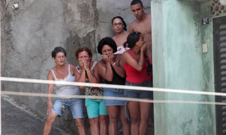 Residents react after a gun battle between police and gang members set a house on fire at the Complexo do Alemao slum in Rio.