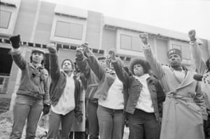 Mourners of MOVE members killed in the bombing by the Philadelphia Police stand in front of their former headquarters. They raise their arms with the Black Power salute as the funeral procession for leader John Africa passes.