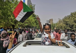 A young girl flashes the victory sign and holds the national flag during a rally near the military headquarters