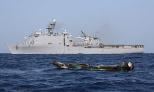 The burned-out hull of a suspected pirate skiff drifts near the USS Ashland after the gun battle in which Mohamed Hassan Farah.