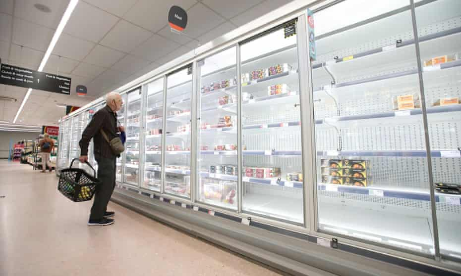 A shopper stares at empty shelves of the Co-op meat aisle in Harpenden, Hertfordshire.