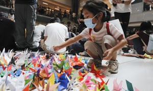 A child arranges origami cranes in the pro-democracy rally at a Sha Tin shopping mall on Sunday