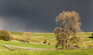 the distinctive drystone walls of Chelmorton against a dark grey sky