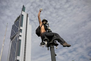 A demonstrator sits on a street light as protests against high living costs continue