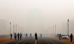 People walk in front of the smog covered India Gate war memorial in Delhi, India.