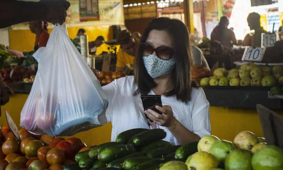 A woman, wearing a protective mask as a precaution against the spread of the new coronavirus, buys vegetables at a market in Havana, Cuba, on Tuesday.