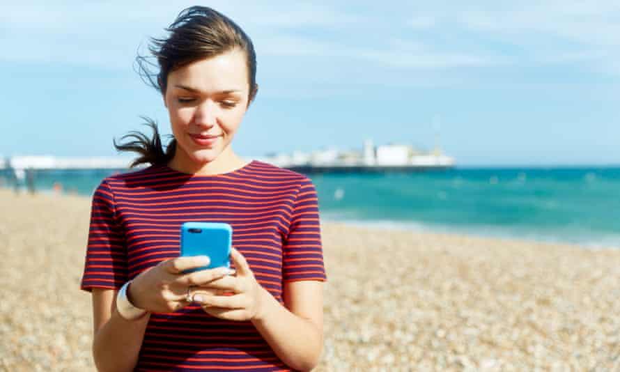 Woman using smart phone on beach