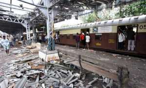 Indian commuters walk past site of explosion at Mahim railway station in Mumbai, July 2006