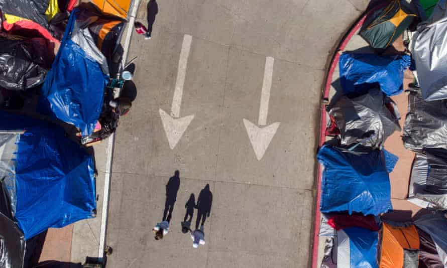 Aerial view of three migrants casting their shadow on the pavement by a migrants camp where asylum seekers wait for US authorities to allow them to start their migration process outside El Chaparral crossing port in Tijuana, Baja California state, Mexico on March 17, 2021.