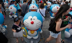 Fans pose with figures of Doraemon at an exhibition in Hong Kong.