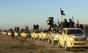 Isis militants hold up their weapons and wave flags on their vehicles in a convoy on a road leading to Iraq, in Raqqa, Syria.