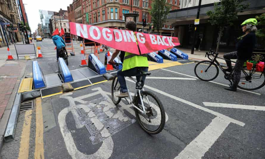 A cyclist rides along Deansgate in Manchester with a banner, after the road was closed to traffic in a plan to pedestrianise parts of the city centre.