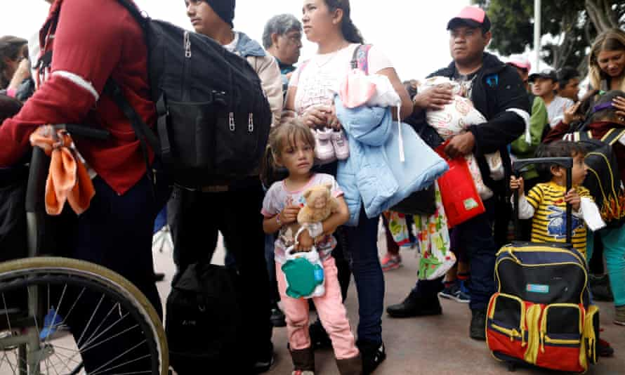 People from the caravan wait at the San Ysidro border crossing in Tijuana, Mexico.